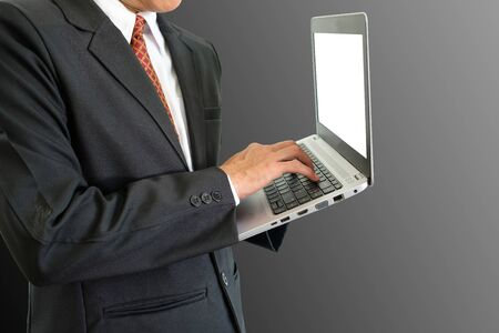Businessman is typing on keyboard computer laptop on gray background