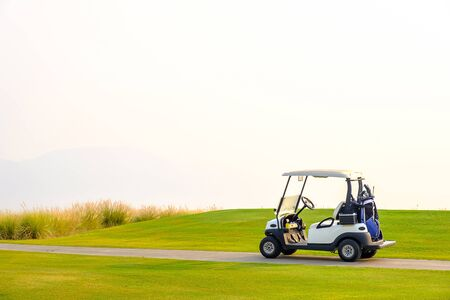 Golf carts on the green yard in the morning.