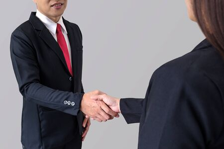 Businessman smile and shake hands with businesswoman on gray background with clipping path.