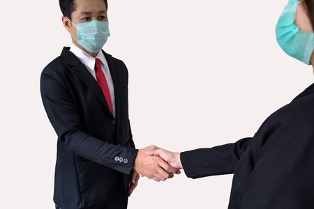 Businessmen wear protect mask and shake hands on gray background with clipping path. 版權商用圖片
