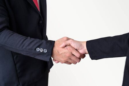 Two businessmen shake hands on gray background with clipping path.