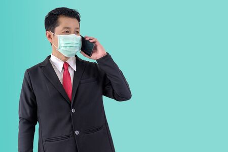 Businessman wear protective mask when using phone for contact business on green background with clipping path.