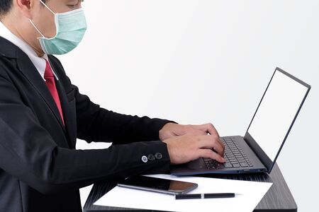 Businessman wear protective mask when he is typing report with computer on gray background with clipping path. 版權商用圖片