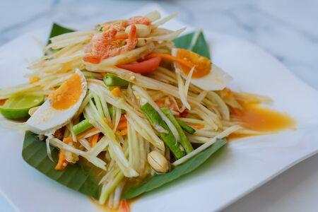 Closeup papaya salad with salted egg in dish on table. 版權商用圖片