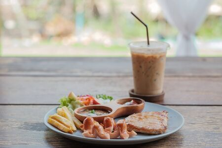 Sausage and pork steak in dish put on the table while ice coffee put on back. 版權商用圖片 - 149156999