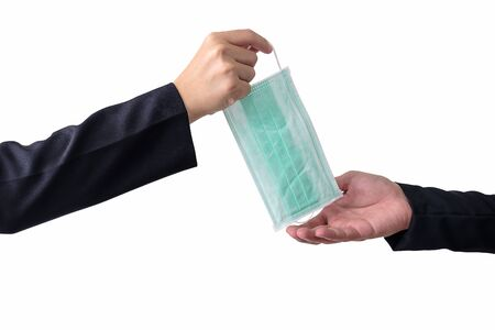 Hand of businessman hold mask and give to someone for protect coronavirus on white background with clipping path.