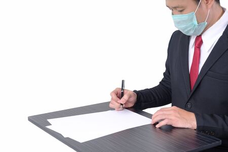 Businessman wear protective mask when he is signing contract on white background with clipping path. 版權商用圖片