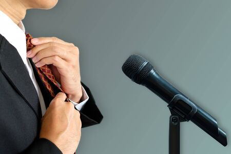 Businessman set tie for prepare to speak with microphone.