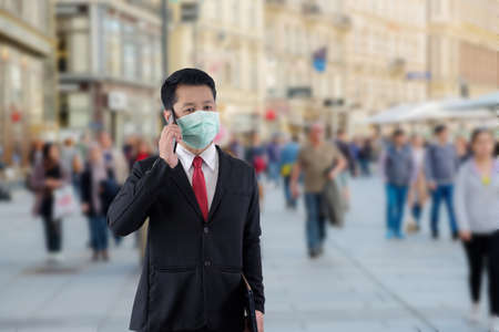 Businessman wears mask and he is talking the phone when he is going to a place with many people.