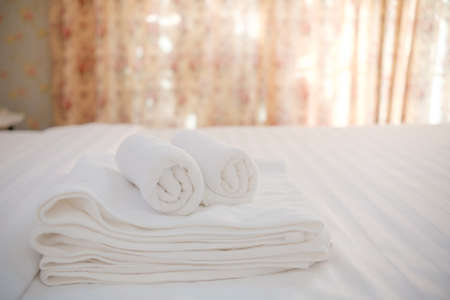 White towels folded neatly put on bed on warm light.