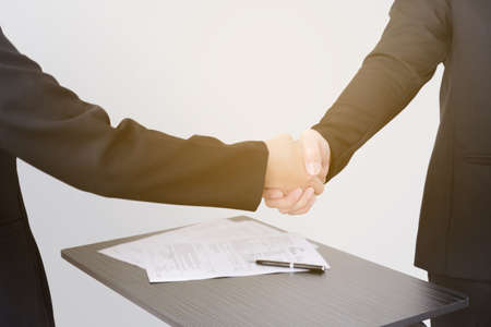Man and woman shake hands after signed contract.