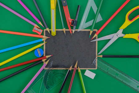 Many school supplies put on black board on green background.