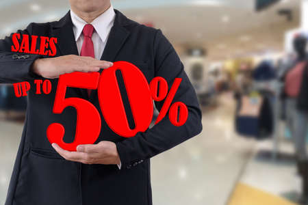 Businessman holds number tell discount fifty percent on department store background.