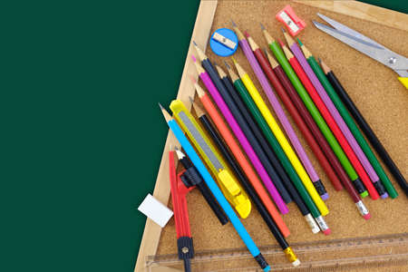 Top view of school supplies on wooden on green background.