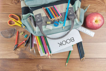 Top view of school supplies in bag on wooden background.