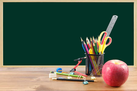 Many school supplies put on the table on blackboard background.