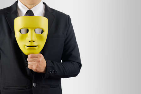 Businessman holds the mask in hand on gray background. 版權商用圖片