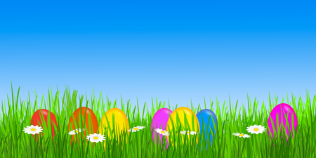 colorful easter eggs in meadow and blue sky
