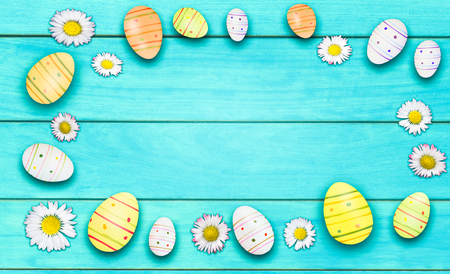 daisies and easter eggs on wooden cyan background