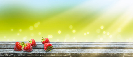strawberries on wooden table on abstract background