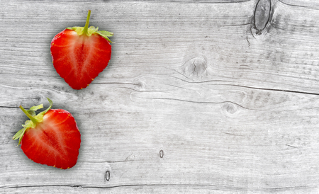 two half strawberries on wooden background