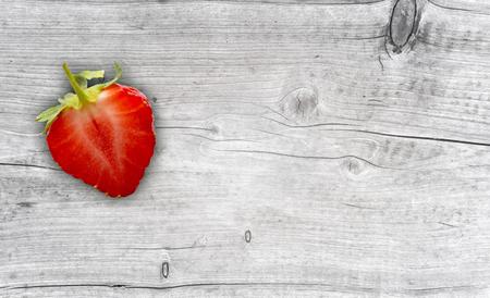 one half strawberry on wooden background