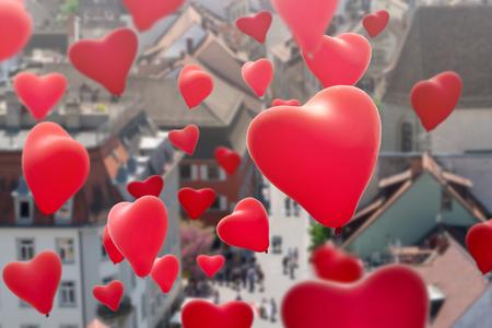 flying heart shape balloons over the city