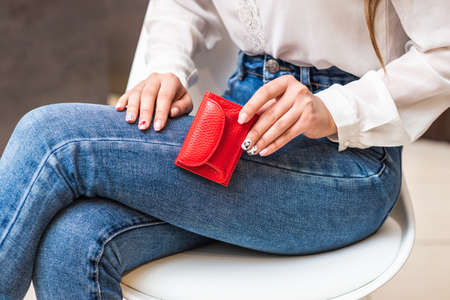 Girl in jeans holds a red little purse 免版税图像