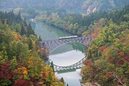 First bridge and Tadami river in beautiful autumn season with train crossing the bridge.