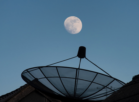 Near full moon in late evening with clear blue sky and sattellite dish.