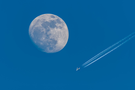 Full moon and flying plane with clear blue sky.