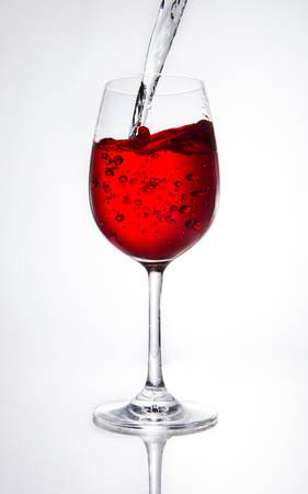 poured: Red wine being poured into glass on white background