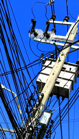 Energy and technology: electrical post by the road with power line cables