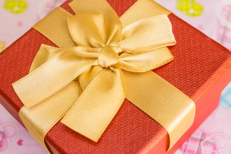 Red gift box with golden ribbon on table photo