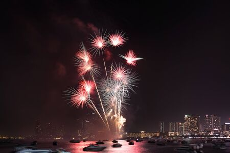 Cityscape of night skyline Pattaya City and Colorful fireworks. Celebration and anniversary concept. Pattaya International Fireworks Festival 2019 at Pattaya beach on twilight background, Thailand.