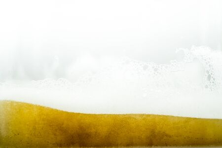 Close up of cool lager beer splash isolated on white background with realistic bubbles & froth in glass. Pouring golden craft beer on front view wave curve shape texture foam for pub & bar menu design