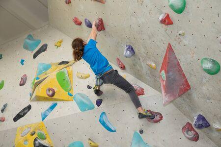 Enfant sur un mur d'escalade , Jeune garçon Bouldering Banque d'images