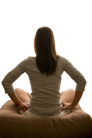 woman on couch: Asian woman sits back cross-legged on couch