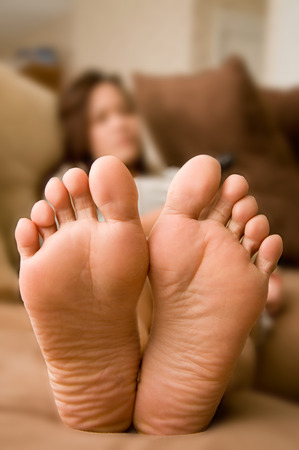 Young asian woman laying on couch.focus on barefoot