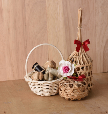 Thai traditional dessert in wicker bamboo basket On wood background.