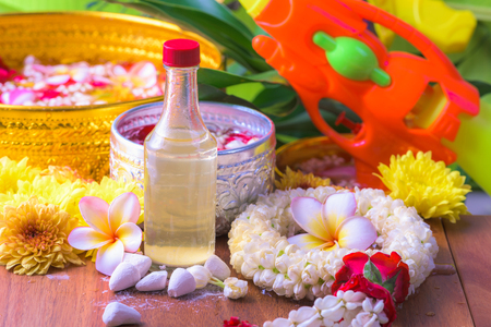 Thai traditional jasmine garland and Colorful flower in water bowls decorating and scented water, perfume, marly limestone, pipe gun for Songkran Festival or Thai New Year.