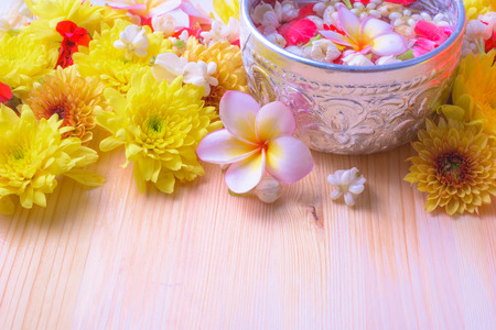Thai traditional jasmine garland and Colorful flower in water bowls decorating and scented water, perfume, marly limestone, pipe gun on wood background for Songkran Festival or Thai New Year.