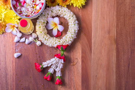 Thai traditional jasmine garland and Colorful flower in water bowls decorating and scented water, marly limestone, pipe gun on wood background for Songkran Festival or Thai New Year. Stock Photo