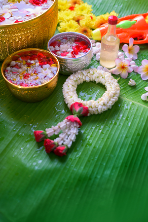 Thai traditional jasmine garland and Colorful flower in water bowls decorating and scented water , marly limestone, pipe gun on Banana leaf for Songkran Festival or Thai New Year.