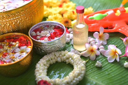Thai traditional jasmine garland and Colorful flower in water bowls decorating and scented water, perfume, marly limestone, pipe gun on Banana leaf for Songkran Festival or Thai New Year. Stock Photo