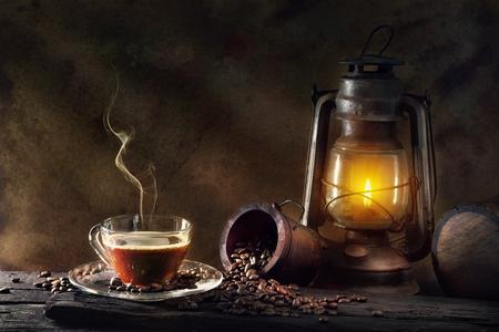 Coffee cup glass and vintage kerosene lamp oil lantern burning with glow soft light aged wood floor. Archivio Fotografico