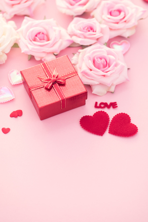 Valentine Day gift box with red hearts and roses on pink background.