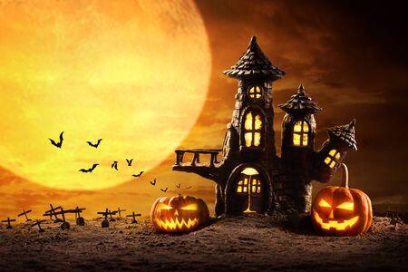 Calabazas de Halloween y castillo espeluznante en la noche de luna llena y murciélagos volando.