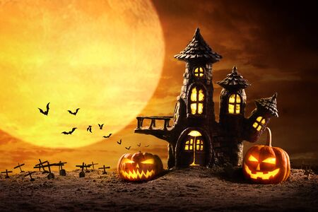 Halloween pumpkins and Castle spooky in night of full moon and bats flying.