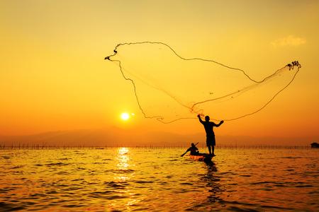 throwing fishing net during sunset Stock Photo